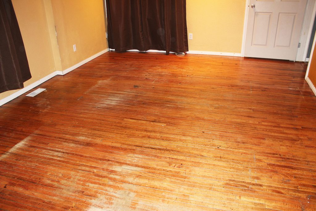 Damaged oak floors before restoration.