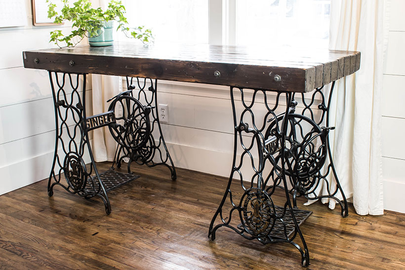 An Industrial desk made from two antique singer sewing machine treadle bases.