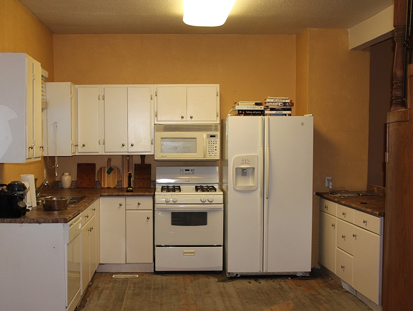 Dated kitchen with old appliances, damaged floors and orange walls.