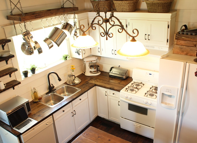an after photo from above of a recently renovated kitchen with bright white cabinets and wood accents.