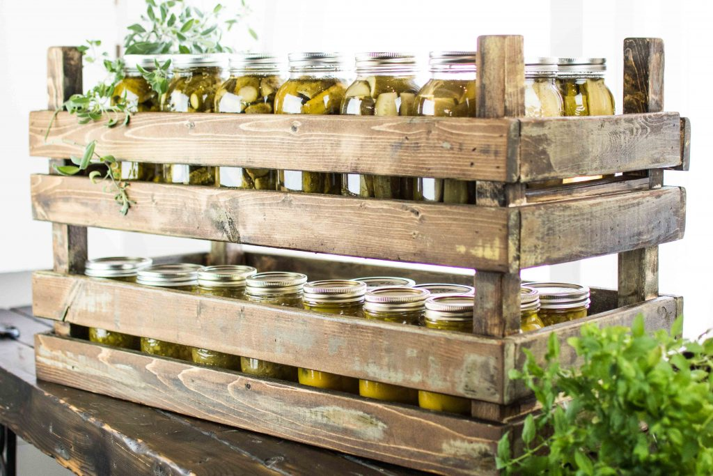 two stacked storage bins on top of one another filled with homemade preserves in mason jars.