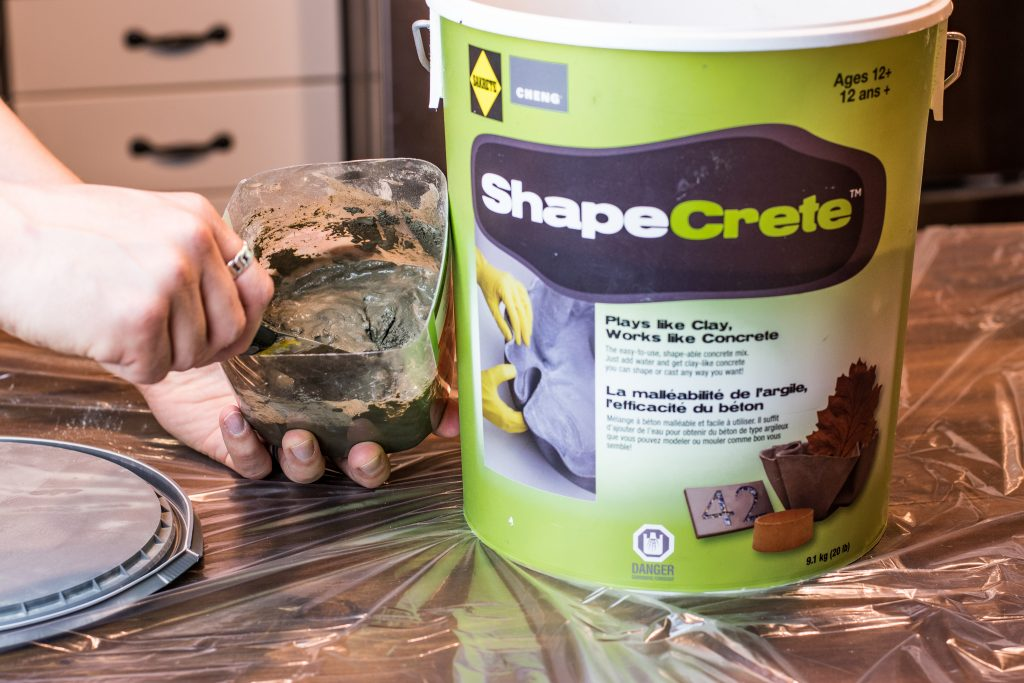 A pail of mixable concrete on table top with someone mixing a small small amount in a clear plastic container.