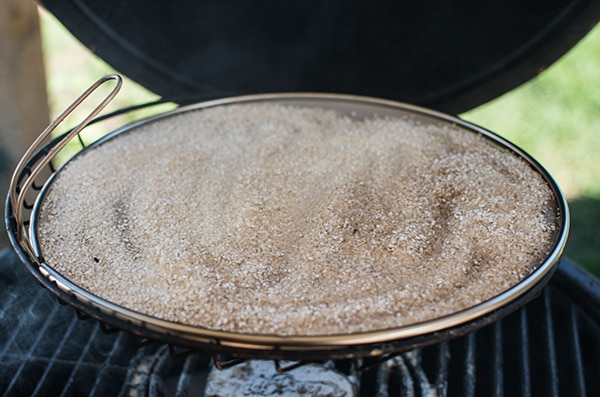 salt on top of the splatter screen on an open smoker