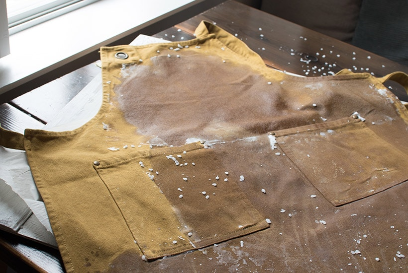 a yellow canvas apron with melted wax everywhere