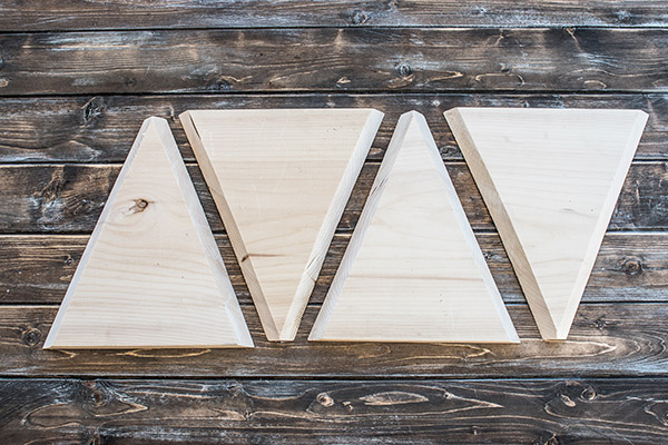 Triangle wood cut outs laid out on a wood board