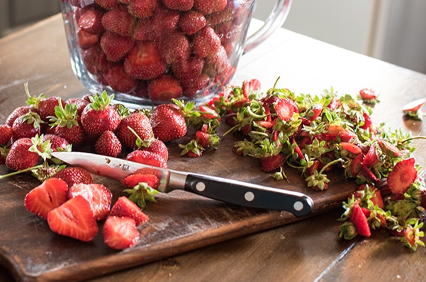 strawberries being hulled and sliced on a wooden cutting board