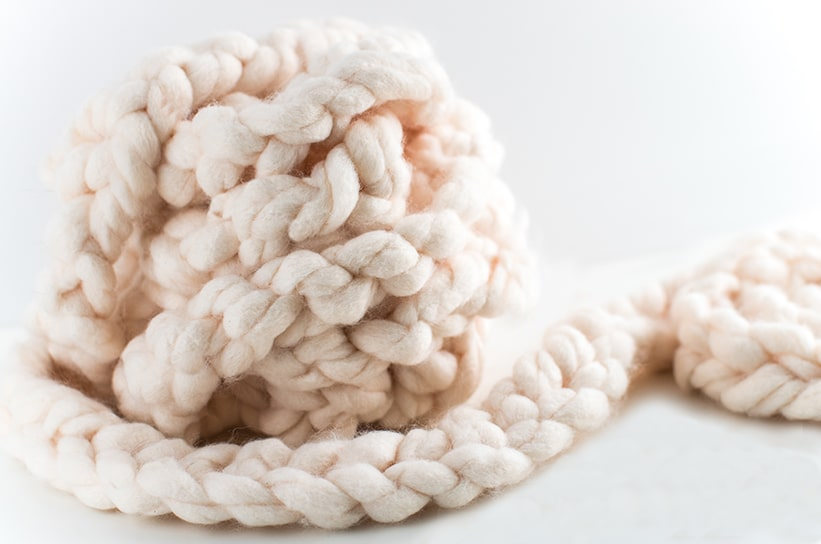 a ball and tail of braided pink jumbo yard against a white background