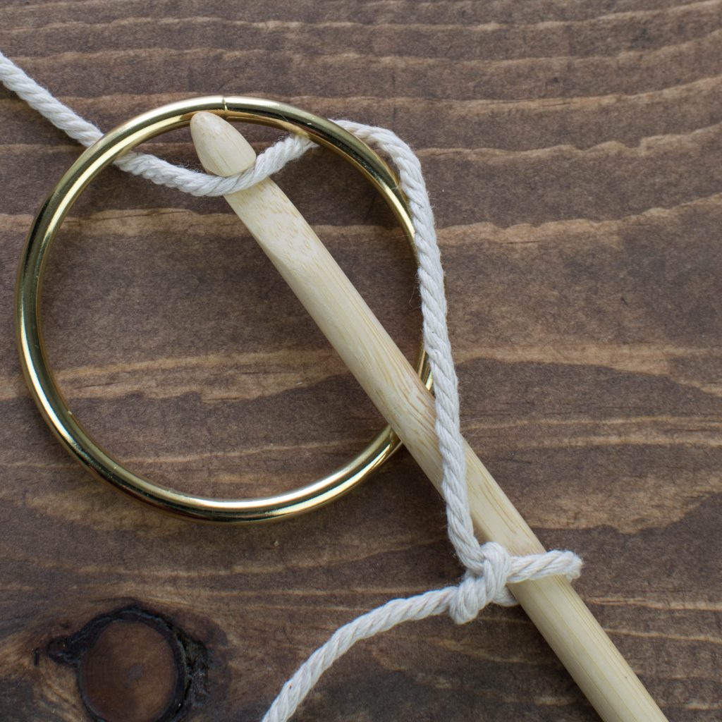 A gold ring, wooden crochet hook demonstrating how to start the first single crochet from the hook to the ring.