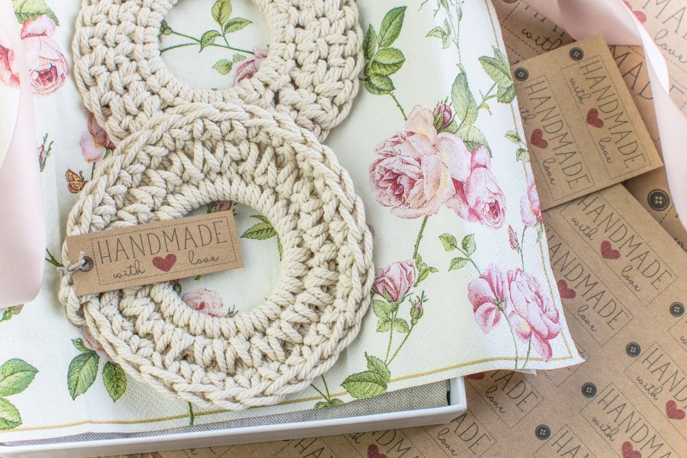 Two white crochet coasters in a gift box with a handmade label