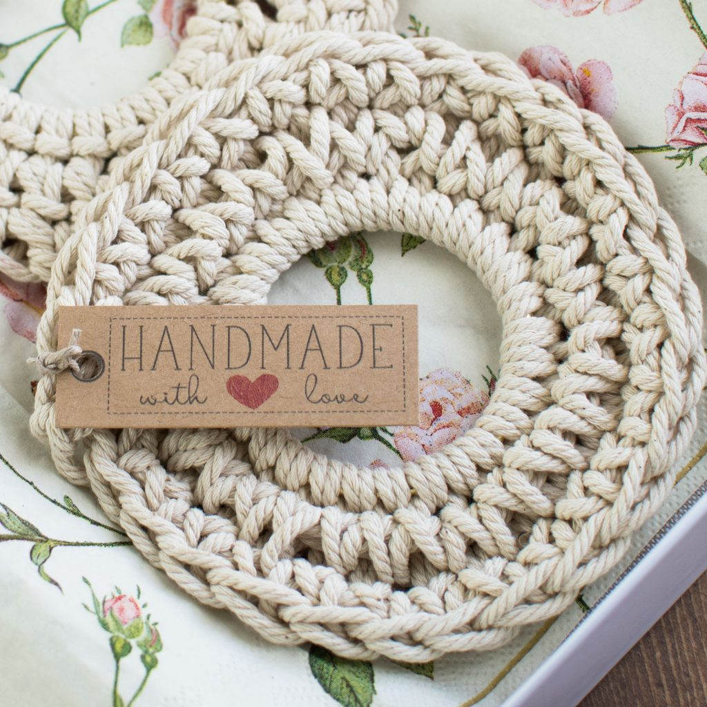 An upclose photograph of a cotton corded crochet coaster with a handmade label