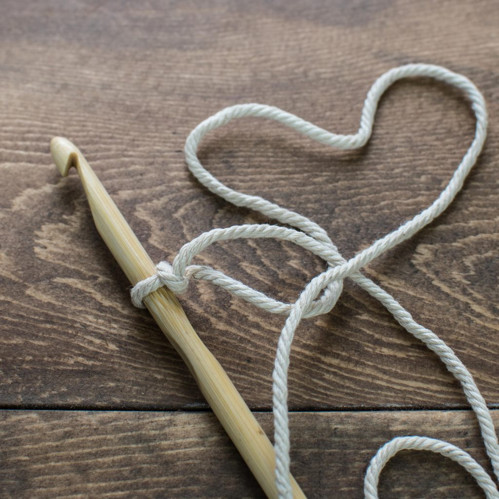A starter crochet loop on a wooden crochet hook on a wooden back ground