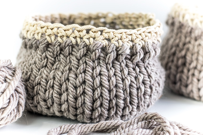DIY baskets grey hand knit with cream trim against a white background