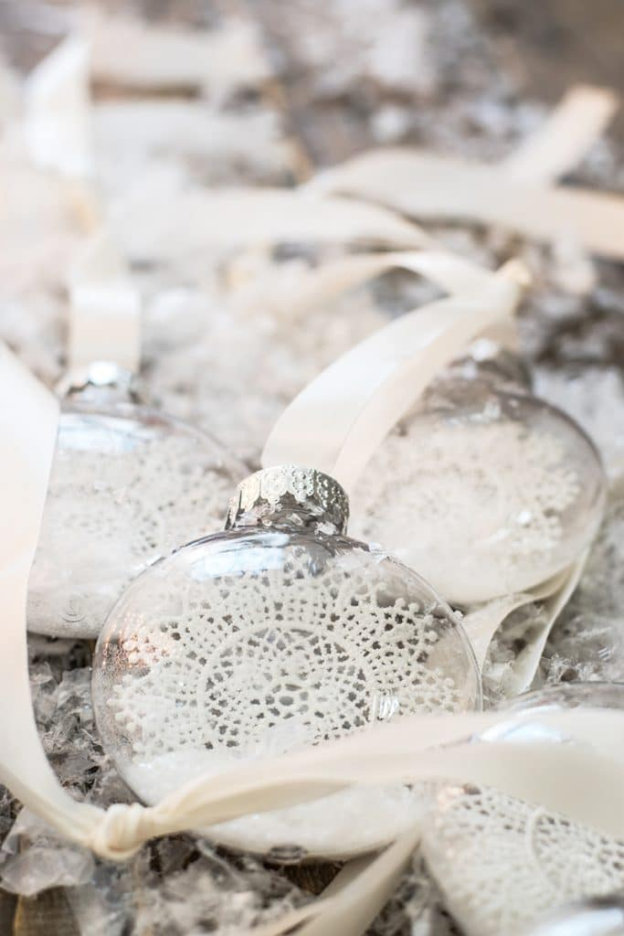 diy christmas ornaments filled with crochet snowflakes, fake snow and glitter, with a white silk ribbon