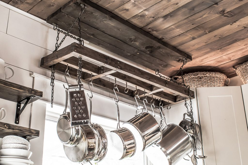 Farmhouse style DIY pot rack hanging in front of a bright window