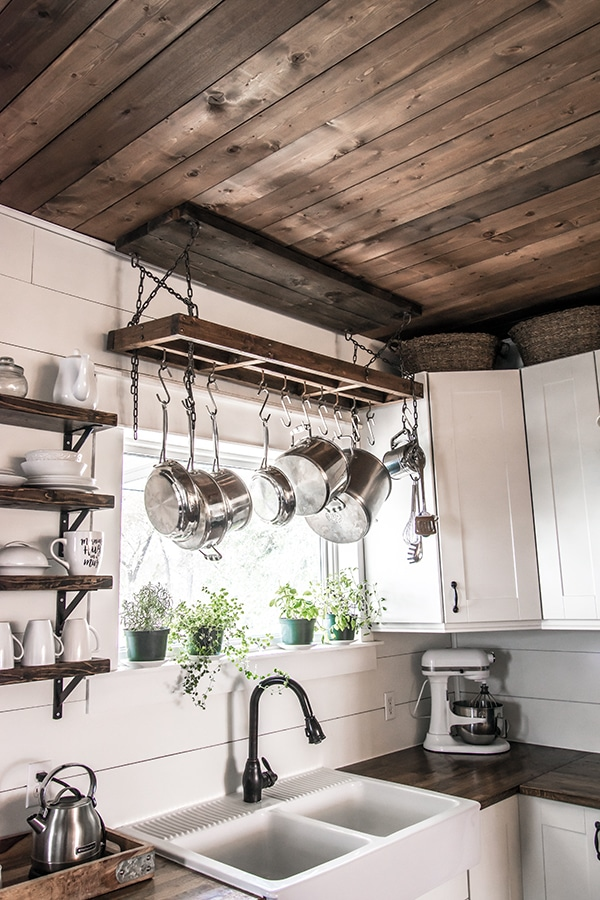rustic farmhouse kitchen with industrial style wooden and metal chain DIY pot rack hanging over a kitchen sink