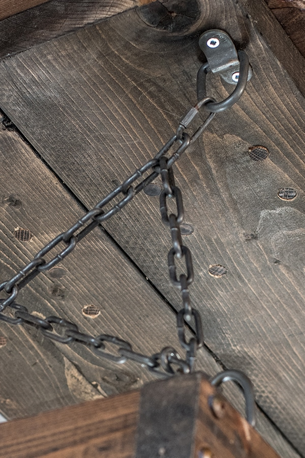 rust and patina covered zinc chains and D ring fasteners on rustic boards