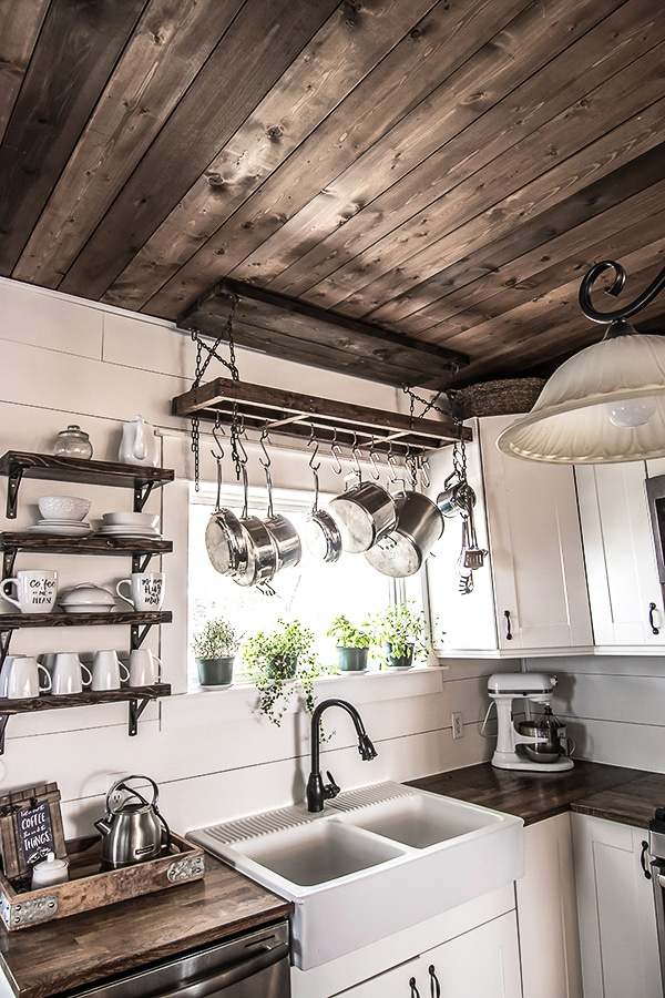 rustic farmhouse kitchen with DIY pot rack hanging from a planked ceiling