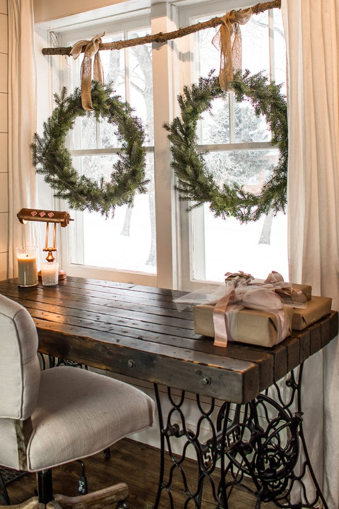 DIY wreaths made from pine hanging on a rustic branch in a tall double set of windows