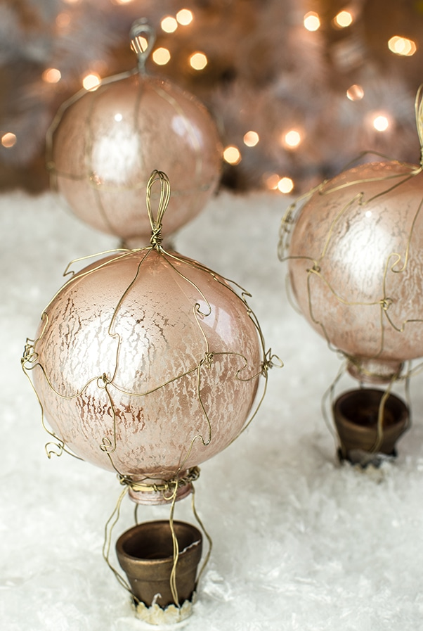 DIY craft french hot air balloon ornaments on a bed of fake snow