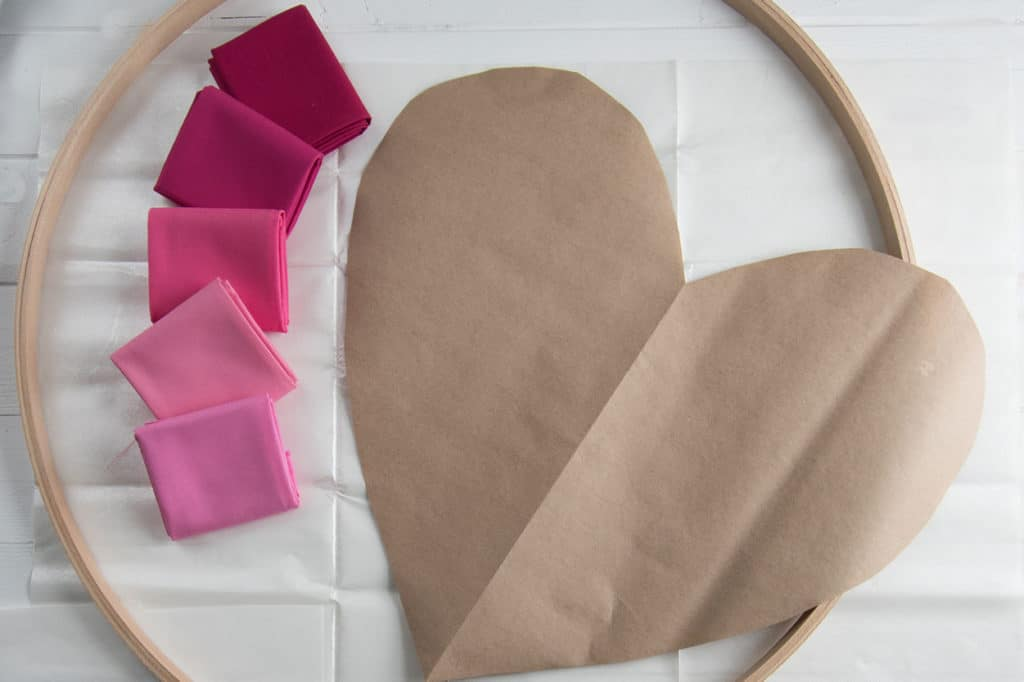 Embroidery hoop, pink coloured fabric swatches and a large kraft paper heart