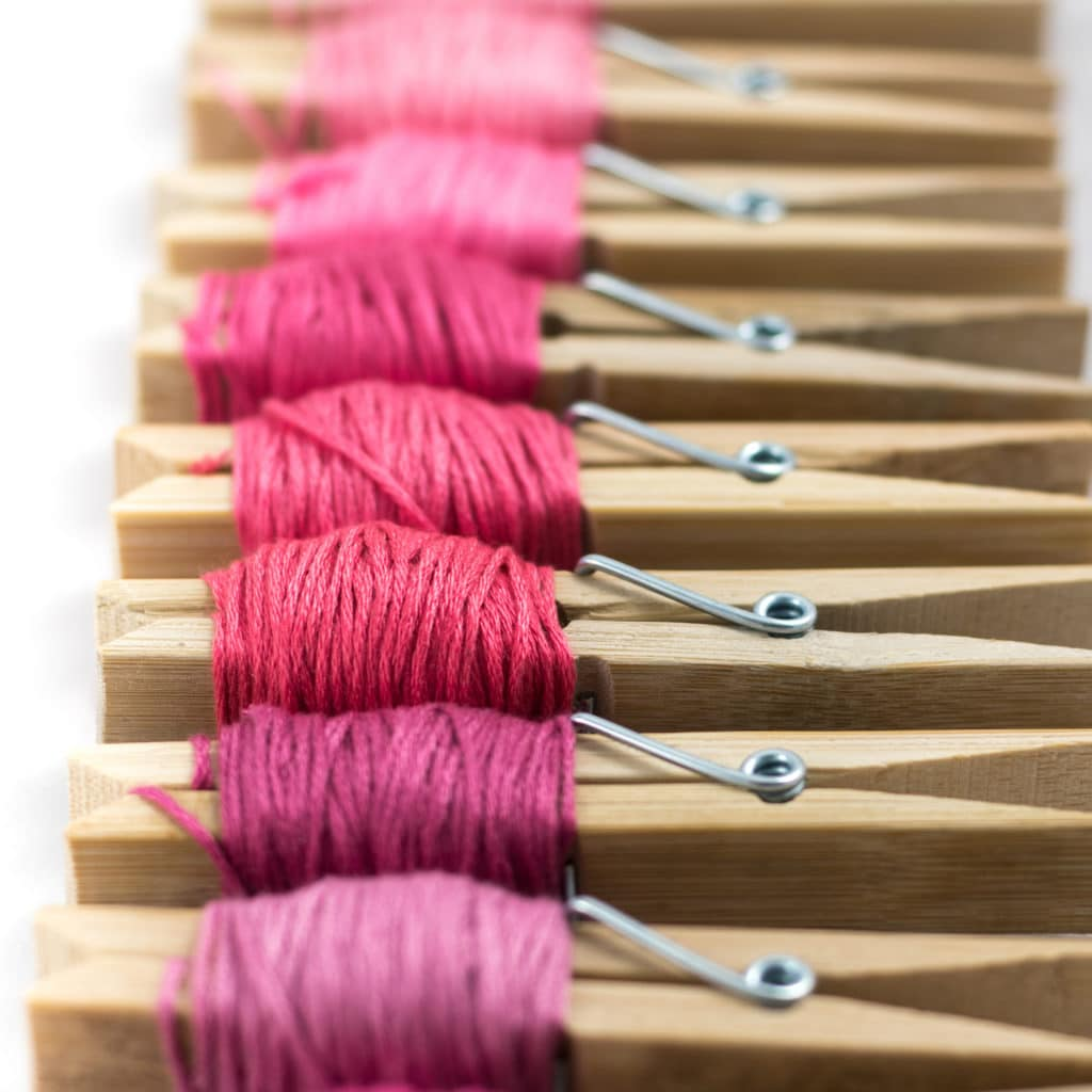 Cloths pins with embroidery floss in various colors of pink