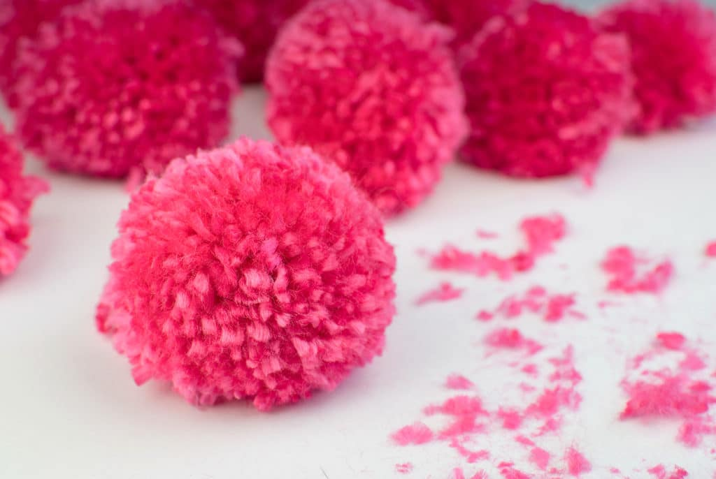 Bright pink pom poms on a white table
