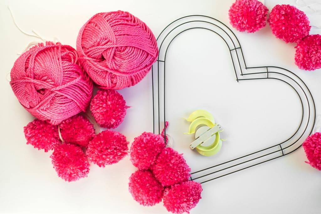 Skeins of pink yarn, pom poms, and a wire heart wreath frame on a white backdrop