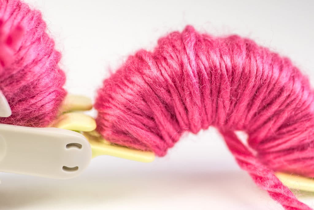 Clover pom pom maker with pink yarn on a white backdrop