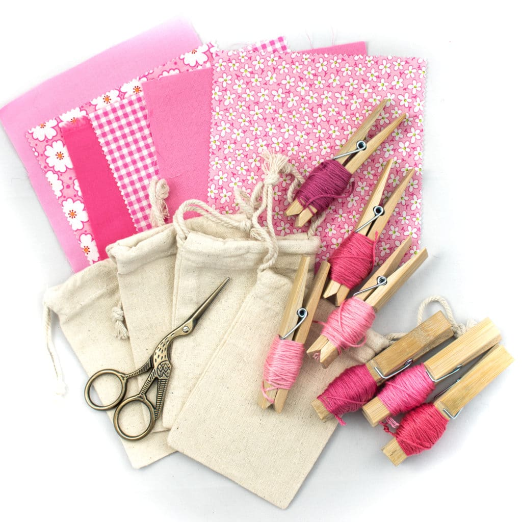 pattern and solid fabric squares in pinks with small canvas tie string pull bags and embrodiery floss