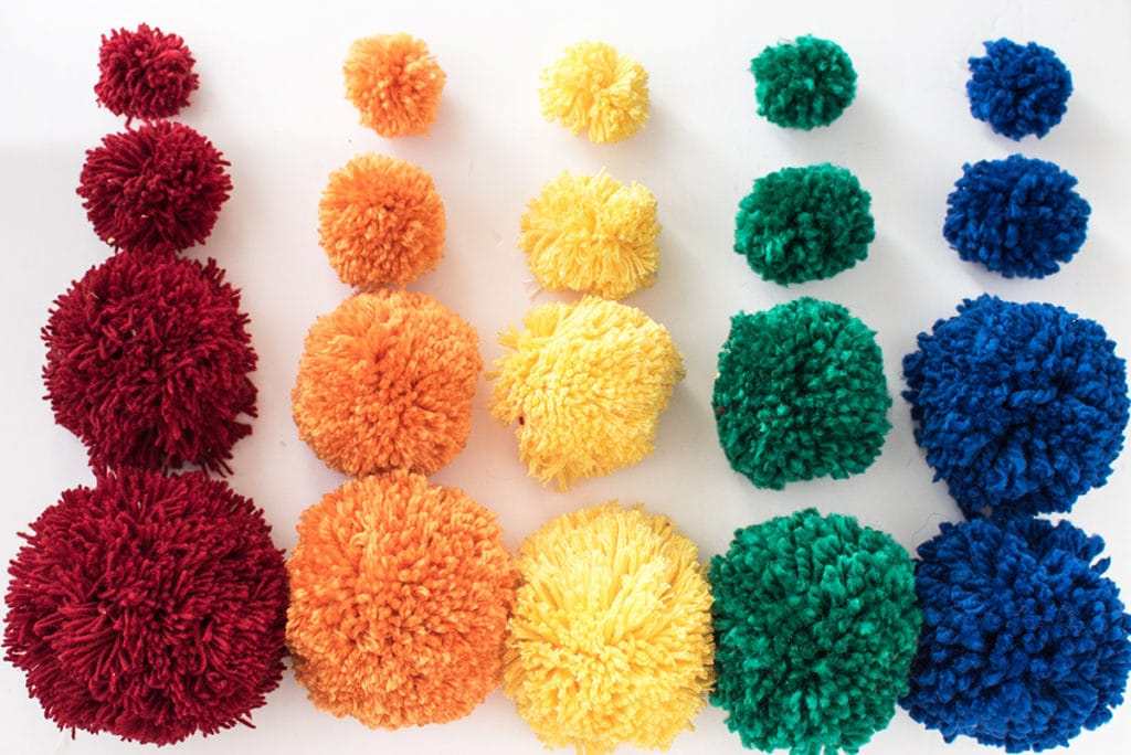 A flat lay comparison of different sized pom poms made with different size wool in rainbow colors