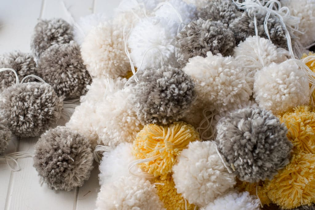 pile of grey, yellow, white and cream pom poms stacked on a white plank table.