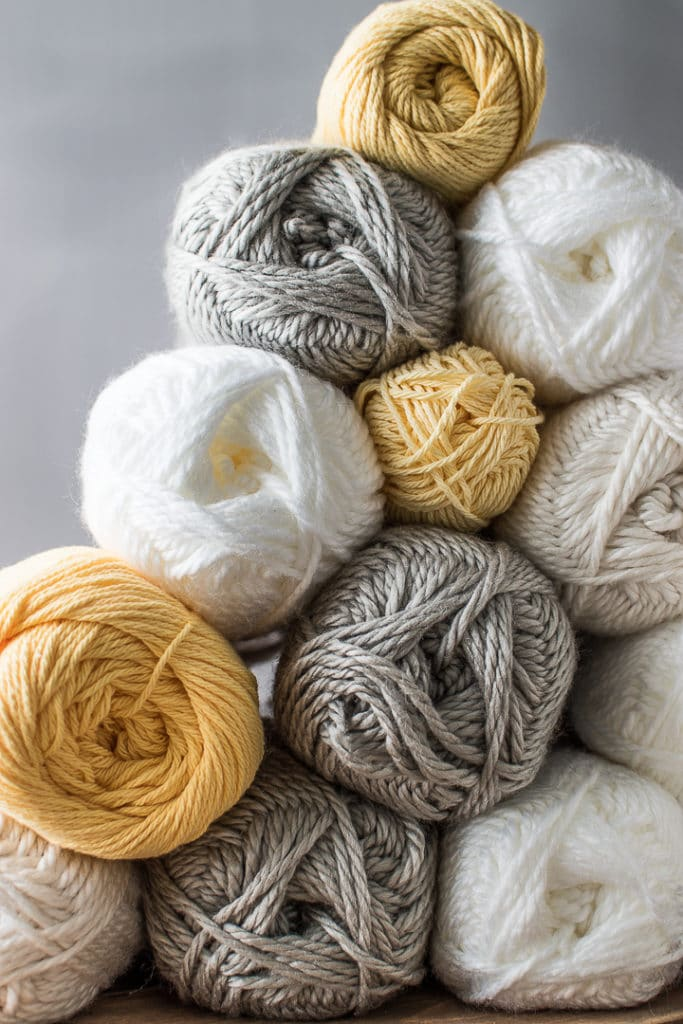 Grey, white, cream and yellow skeins of yarn stacked into a pyramid against a grey background