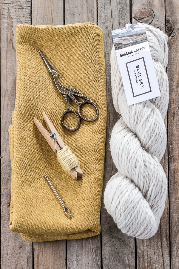 A skien of White cotton yarn, a yellow cushion cover, scissors, and embroidery thread laid out on a grey wood background