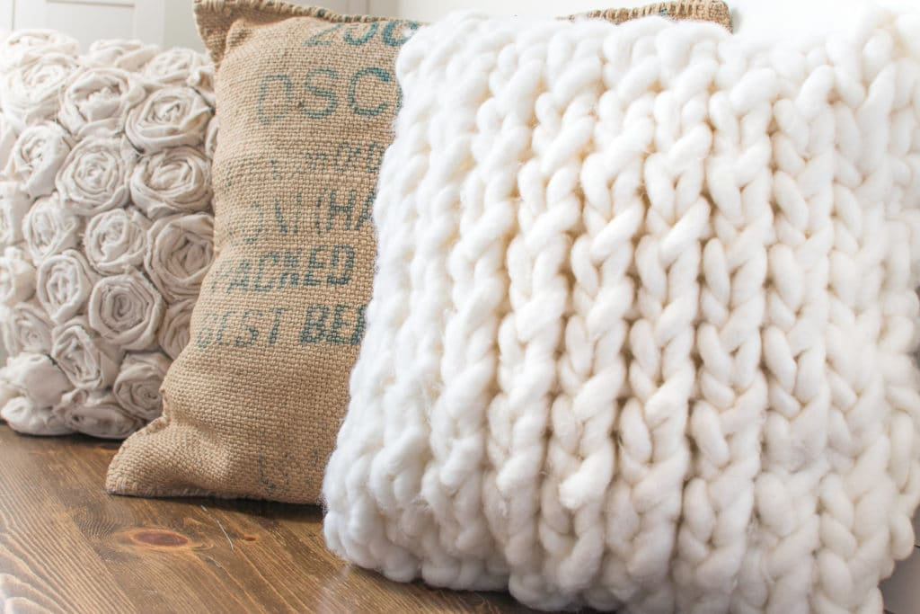 A row of pillows on a wooden surface with a chunky knit pillow in the foreground.