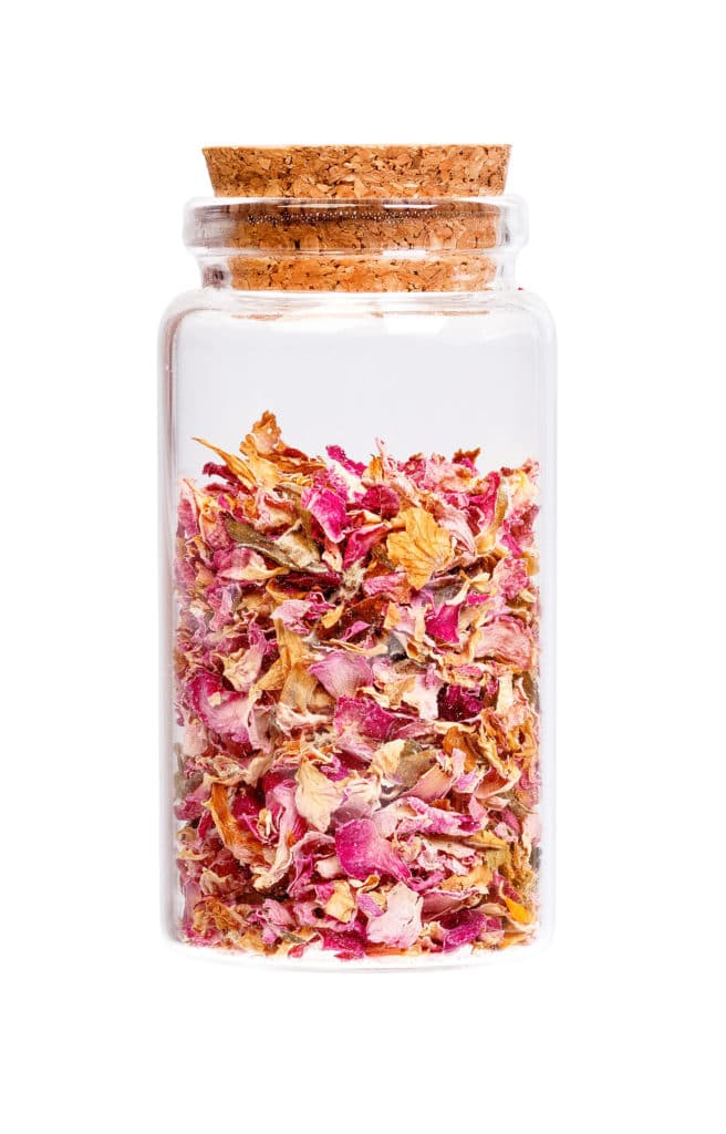 A glass jar with a cork top filled with crumbled dried petals against a bright white background