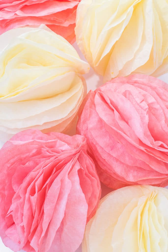 Pink and coral coffee filter paper pom poms on a bright white table