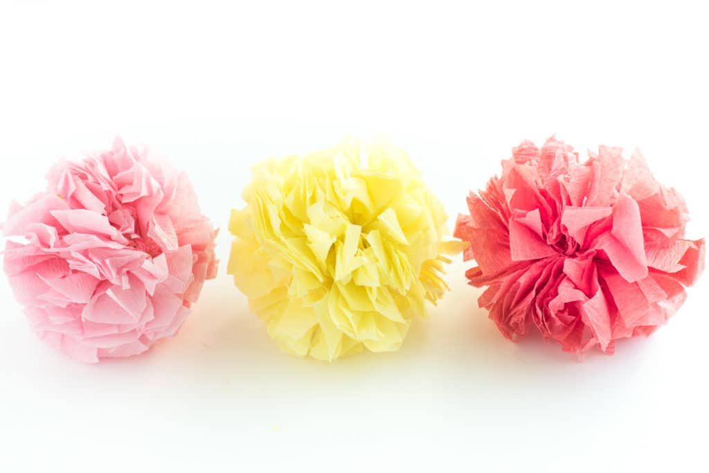 3 small paper pom poms made from crepe paper streamers on a white surface