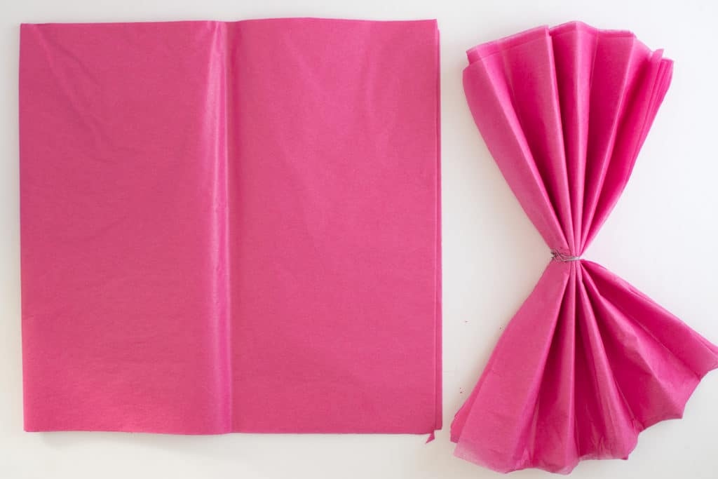 A square set of bright pink tissue paper on a white surface nest to a fan folded square of tissue paper secured in the center with a piece of wire.