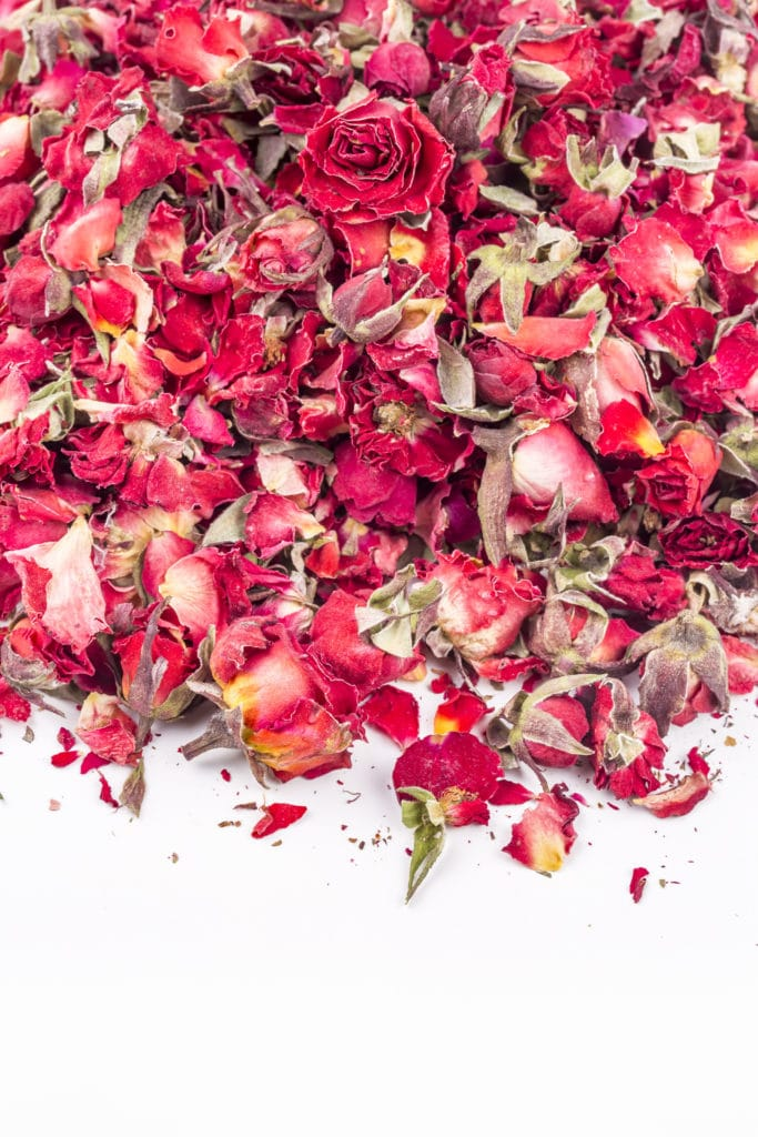 A scattering of red roses and red dried rose petals over a bright white table top