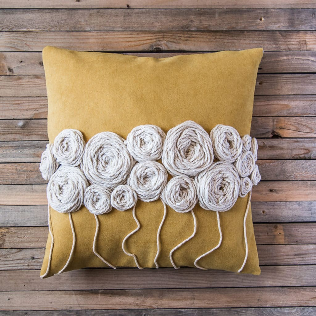Bright yellow cushion with white wool embroidery flowers across the centre.