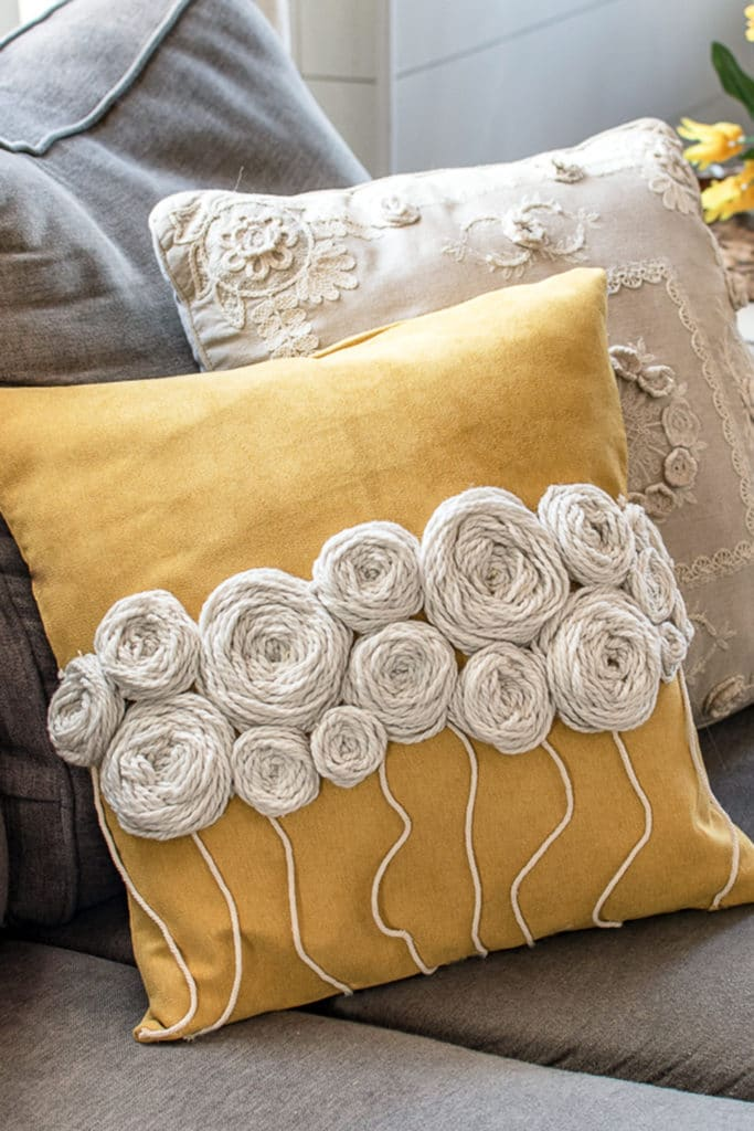 Yellow cushion with white wool embroidery flowers on a grey sofa