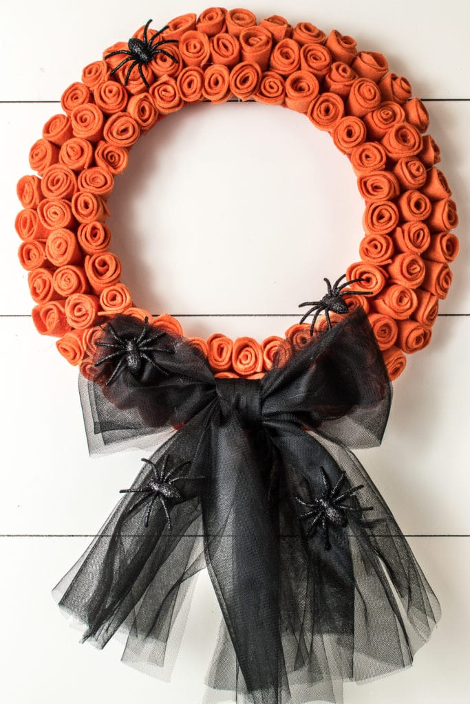 A bright orange rose felt wreath with a big black tulle bow with a few large fake black spiders.