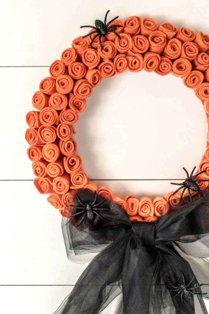 A DIY halloween wreath with orange roses, large black tulle bow and black spiders