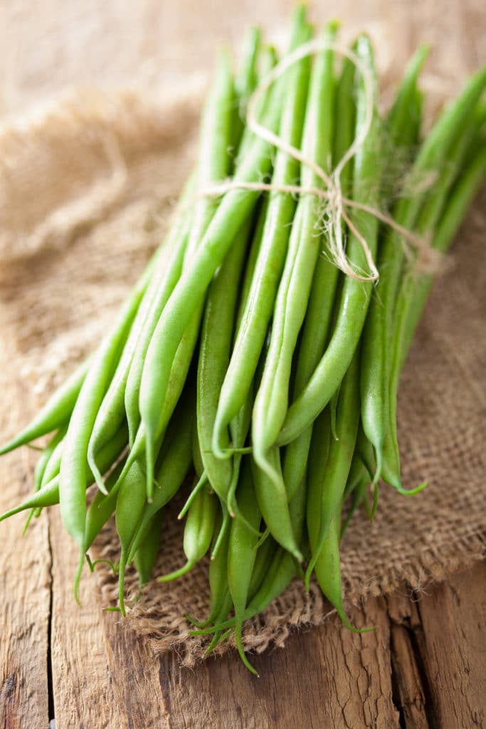 A bundle of fresh green beans wrapped with string on a piece of burlap