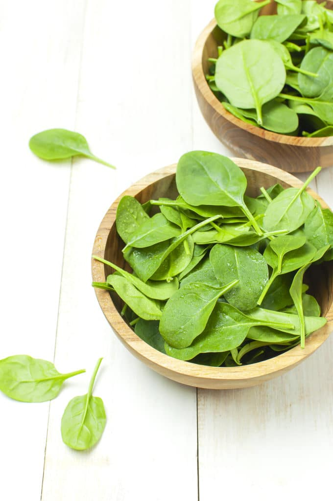 Bowls of freshly picked bright green lettuce in wooden bowls a rustic white table top.