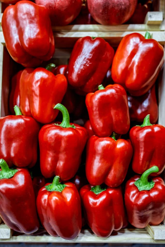 Harvest of bright red bell peppers in a wooden crate