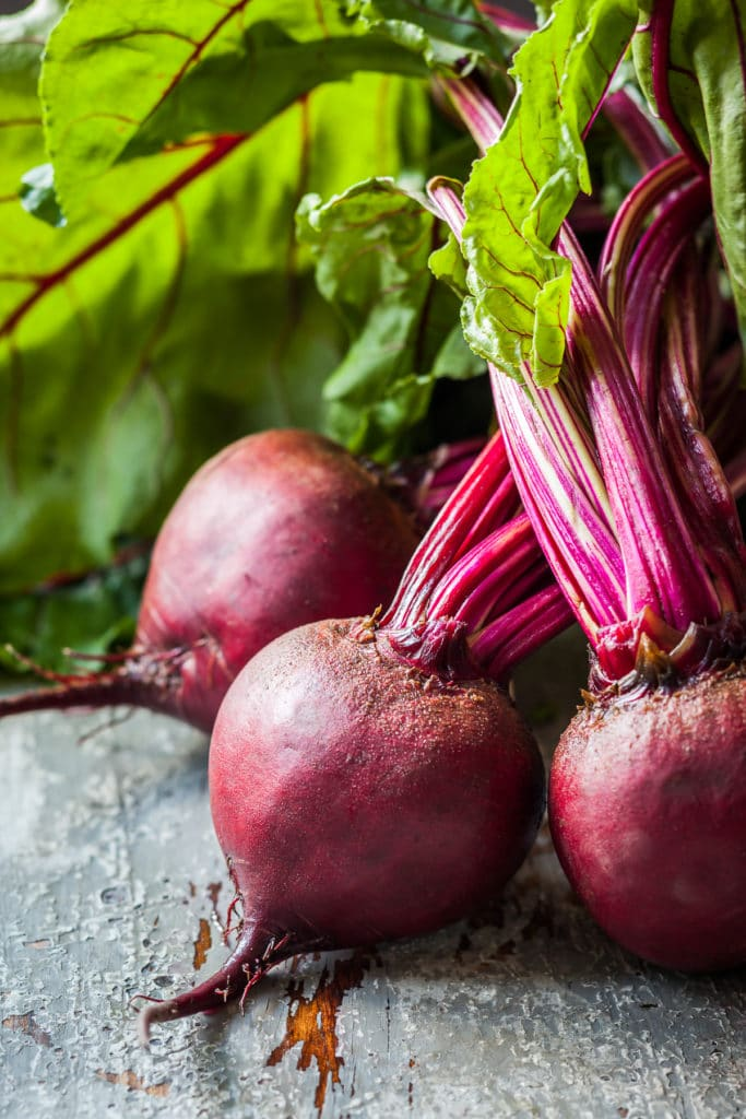 Deep read beets with their bright green tops freshly picked from a summer vegetable garden