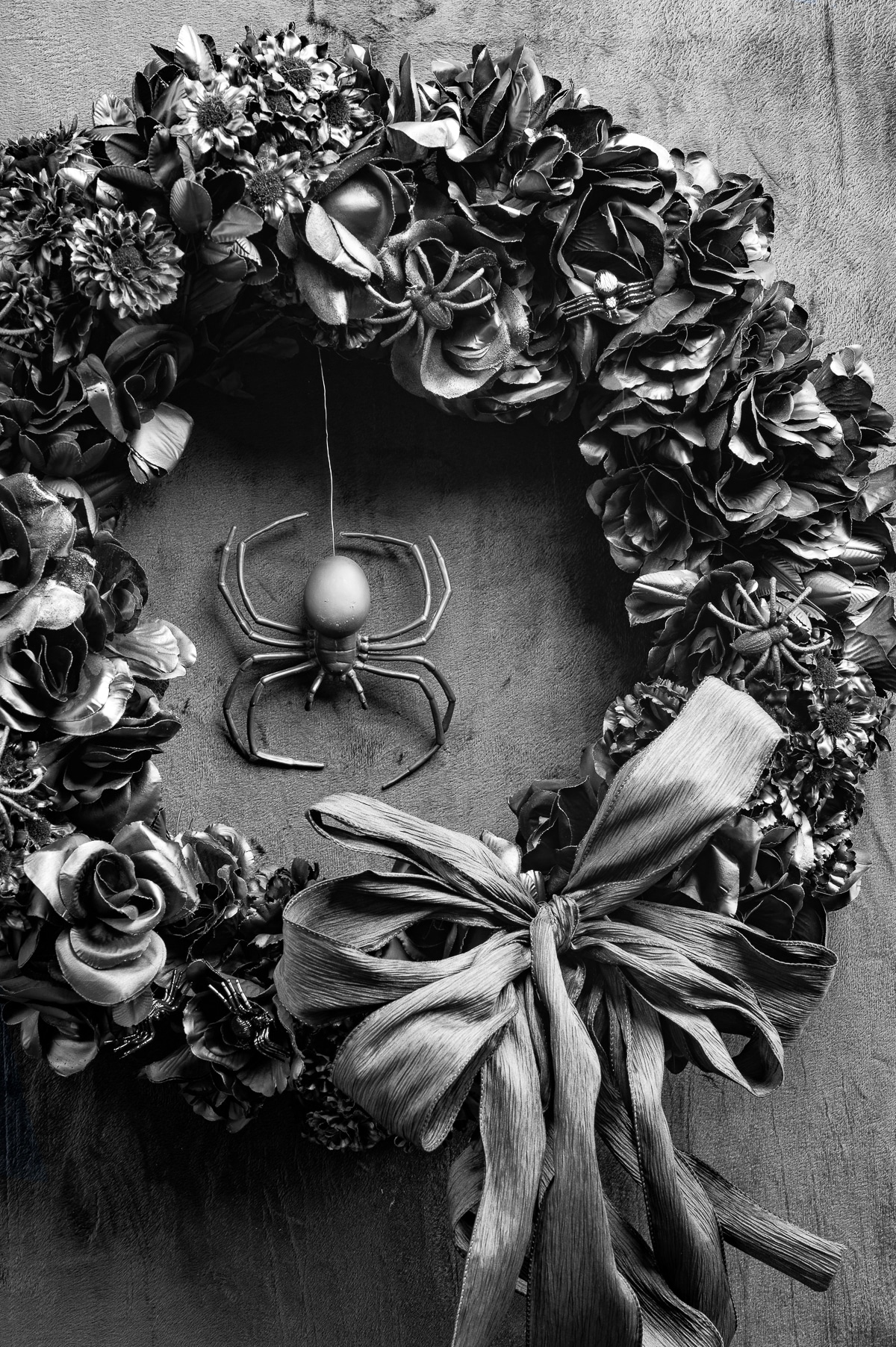 A floral all  black halloween wreath with black bow, and large plastic spider hanging in the centre.  The Wreath is hung on a black velvet background.