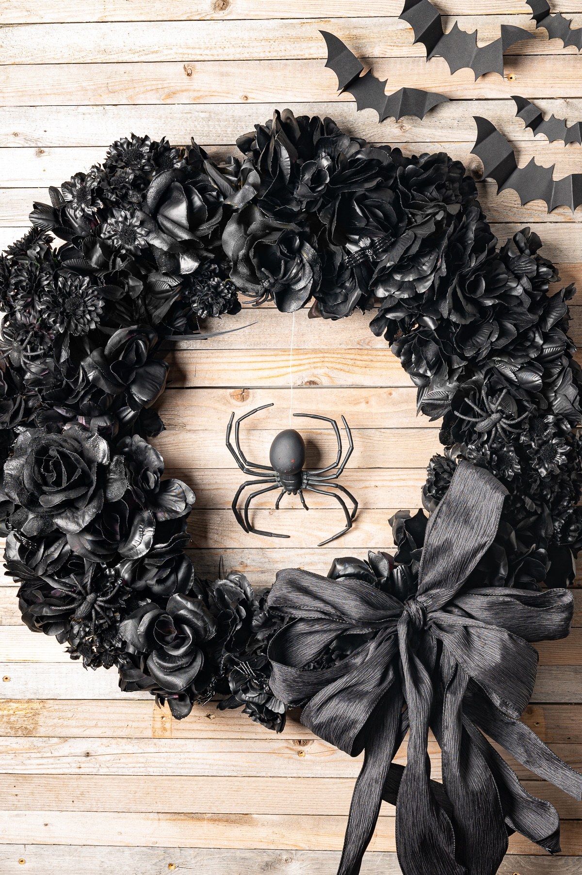 A floral all  black halloween wreath with black bow, and large plastic spider hanging in the centre.  The Wreath is hanging on a rustic pine background with paper bats