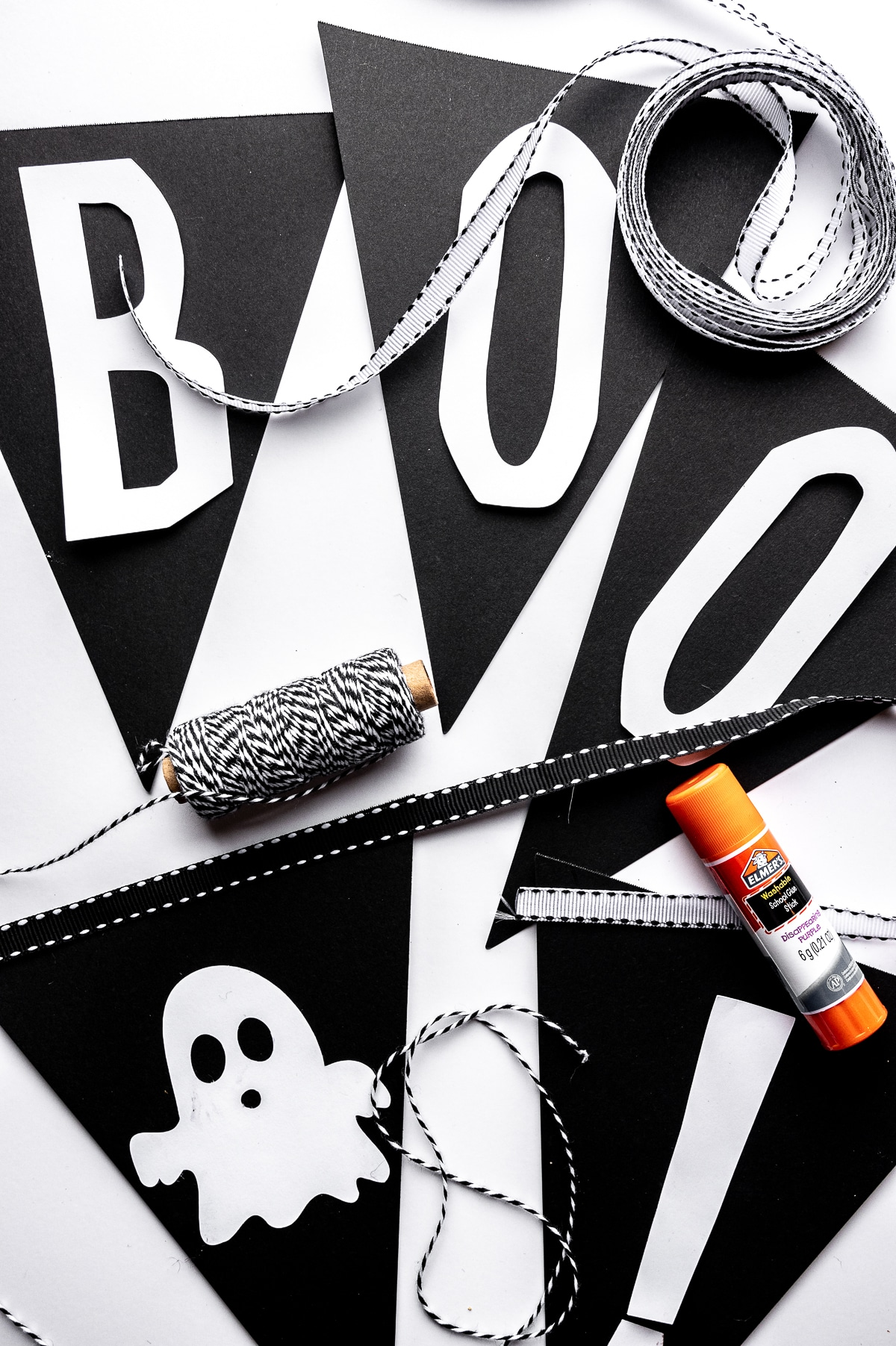 Black cut out triangles with white cut out lettering against a bright white background.  Black butchers twine, white and black ribbon as well as a glue stick surround the cut outs.